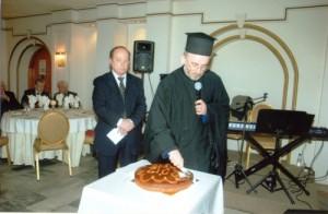 Ο Αρχιμαδρίτης Ιωακείμ ευλογεί και κόβει την πίτα .